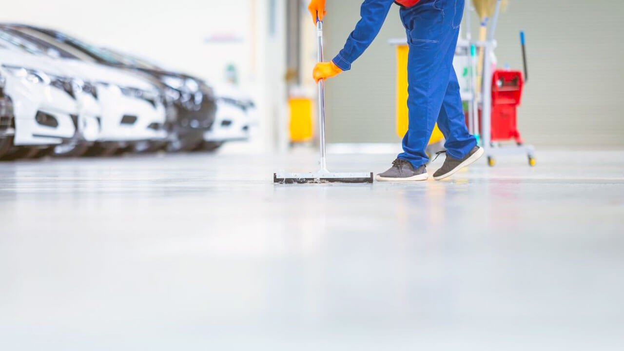 A Car Garage Staff Cleaning The Epoxy Floor